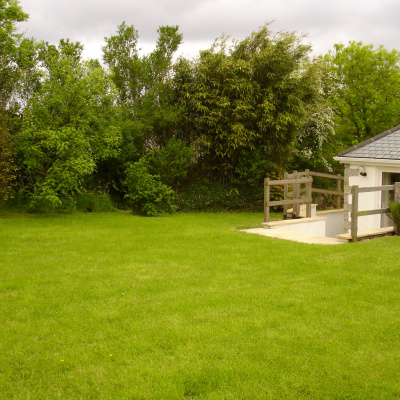 Large secluded back garden with picnic table on lawn, loungers on terrace and swing ball game for the energetic.