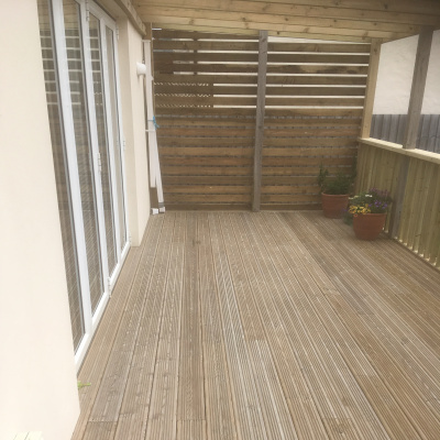 Outdoor decked area with lounge access through bifold doors.